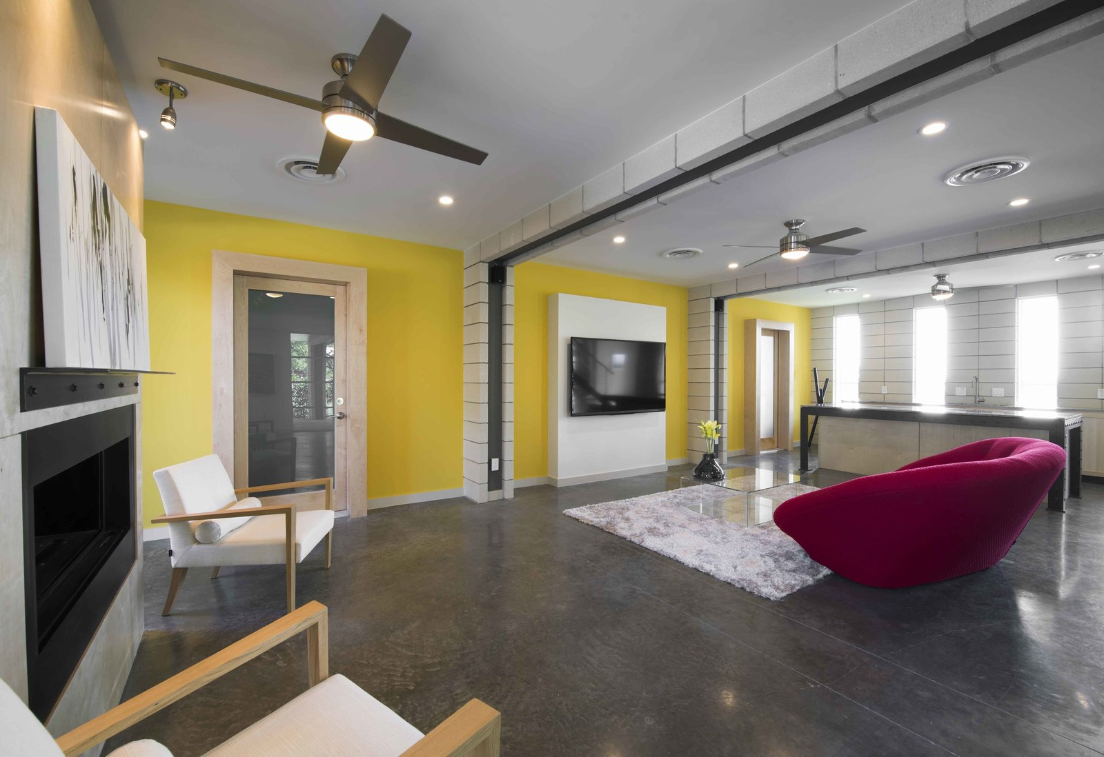 Contemporary, bright accents contrast with the dark concrete floors in the entertainment area.