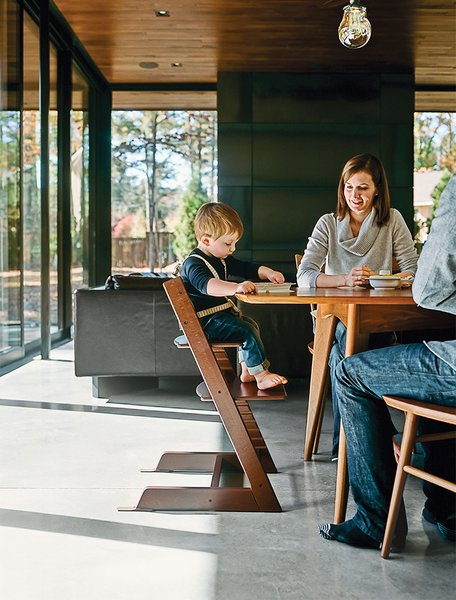 Amy and Jeremy Clark join their son, Edison, in the dining room; the Thatcher chairs by Newport Furniture and a dining table by Caperton of West Virginia are both from Room & Board. Edison's high chair is the Tripp Trapp model by Stokke.