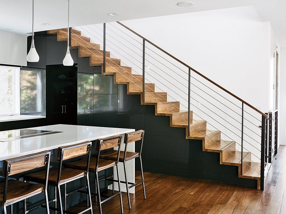 The Dora pendant lights in the kitchen are from Rejuvenation; quartz countertops are by Cambria and the custom bar stools are by Rocky Mountain Table Company. In Situ Studio designed the solid walnut steps with custom steel rails, a walnut hand rail, and a removable baby gate. Tagged: Staircase, Metal Railing, and Wood Tread.  Photo 6 of 13 in Minimal North Carolina Home Built for a Tech-Forward West Coast Couple