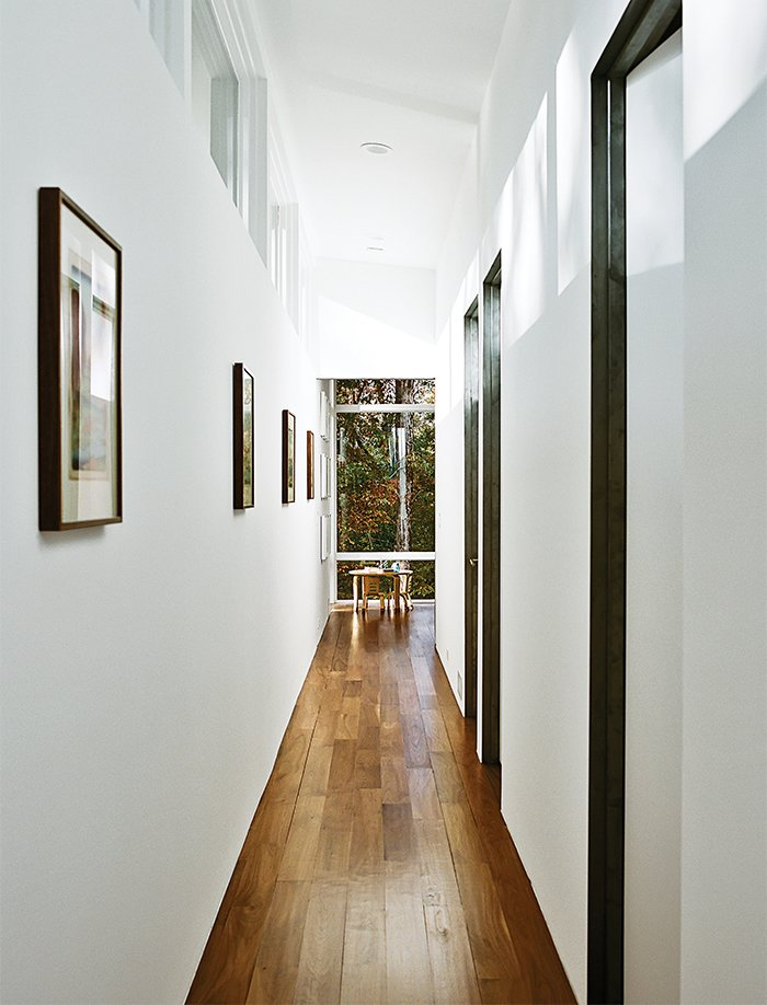 The interiors are painted in Sherwin-Williams Extra White Flat; flooring is five-inch walnut plank. A bentwood table and chairs are from ECR4Kids. Tagged: Hallway and Medium Hardwood Floor.  Photo 9 of 13 in Minimal North Carolina Home Built for a Tech-Forward West Coast Couple
