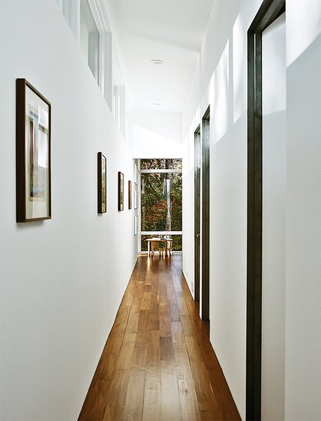 The interiors are painted in Sherwin-Williams Extra White Flat; flooring is five-inch walnut plank. A bentwood table and chairs are from ECR4Kids.  Photo 9 of 13 in Minimal North Carolina Home Built for a Tech-Forward West Coast Couple