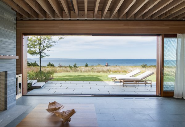 To further connect the indoor spaces with the New England landscape outside, glass walls in the living and dining areas slide open to eliminate the barriers between indoors and outdoors. Green slate tiles compose the flooring inside.
