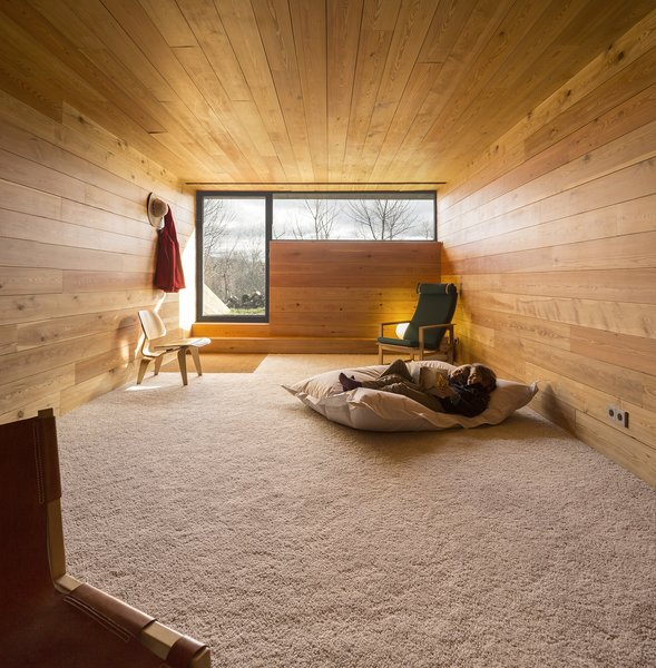 Downstairs, bedrooms and a library offer private spaces. Wide-plank blond wood wraps the walls, floors, and ceilings, creating a cozy shiplike experience. Photo 7 of Refuge modern home