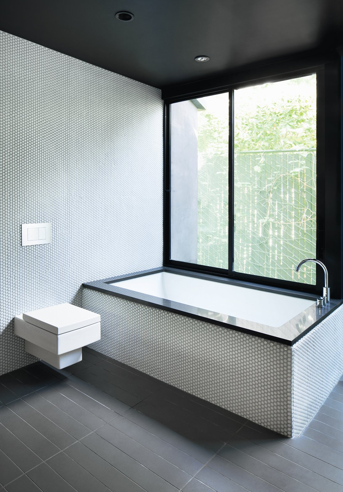 "For the bathroom inside a renovated Hollywood bungalow, architect Noah Walker used a simple palette of gray and white tile, black countertops, and stainless steel fixtures. ""I love minimal bathrooms with natural light, so less is more, and pay attention to the details,"" he advises. Tagged: Bath Room, Ceramic Tile Floor, One Piece Toilet, Recessed Lighting, Ceramic Tile Wall, and Undermount Tub.  Baths by Lara Deam from A Minimalist Bathroom in Los Angeles"