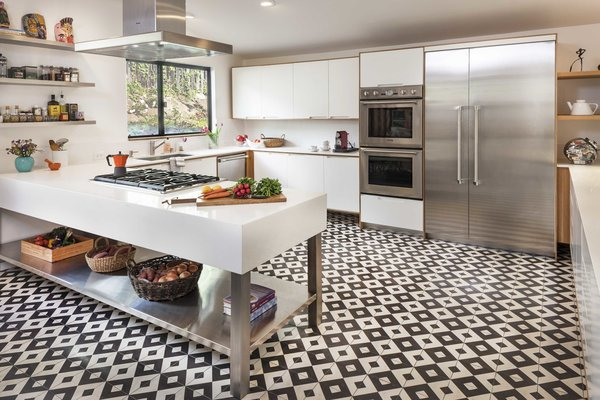 The renovation of the kitchen added 100 square feet to the space, along with larger windows to let in more light. The appliances are Thermador, and the black-and-white floor tile by Granada Tile.