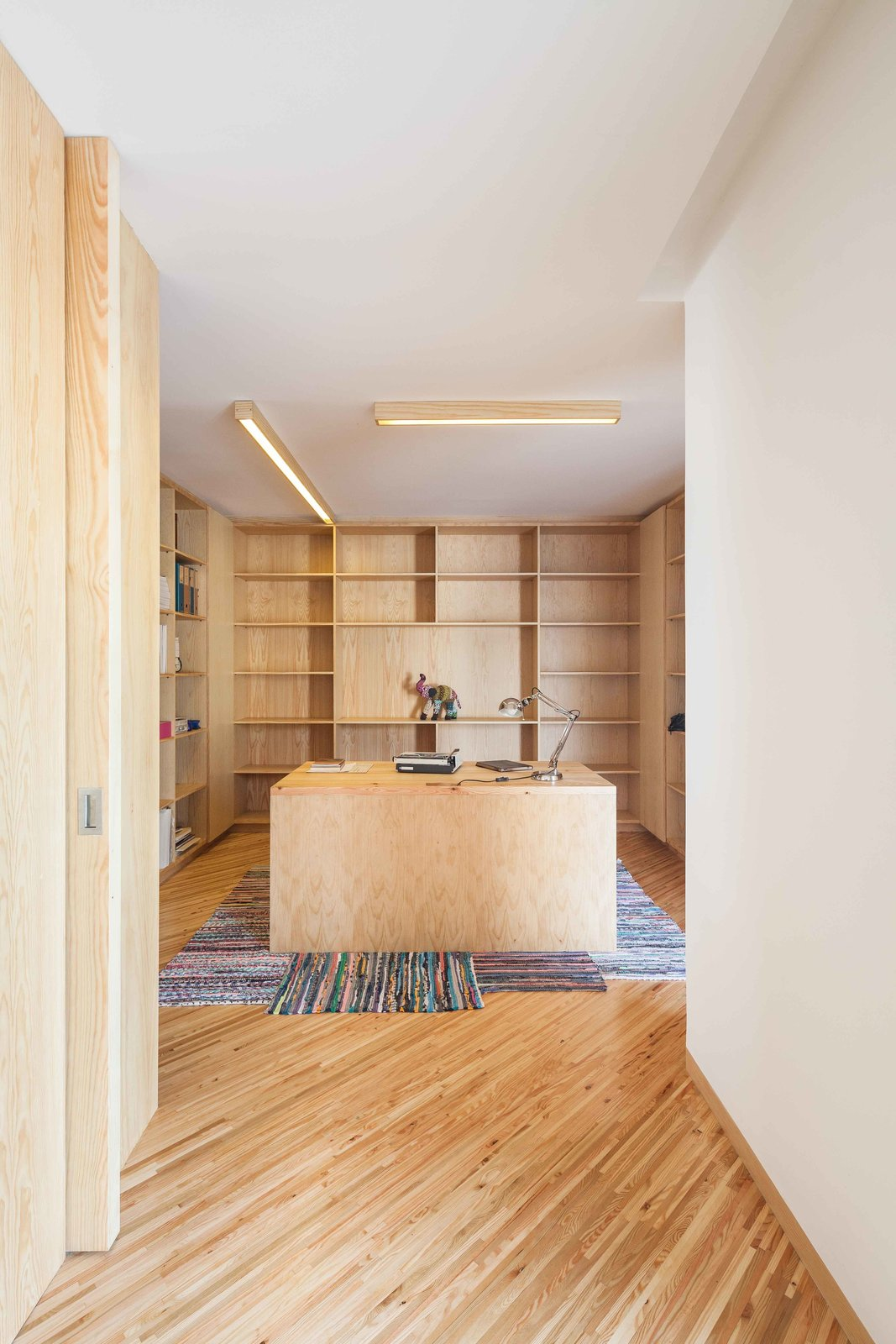 In the study, strip lighting illuminates a desk almost entirely surrounded by built-in bookshelves.  Stuff I like by Chloe Michaelidis from Lovely Beach House is All About Angles, Stucco, and Wood