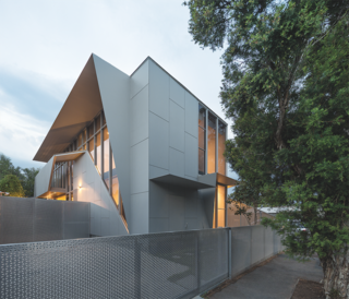 9 Angular Homes Inspired by Geometry - Photo 6 of 9 - This Melbourne house designed by fmd Architects is made up of a simple cement-and-steel box with elements that fold outwards to create privacy screens where needed. A perforated aluminum fence unravels from the building down toward the street. The material was selected to deter local graffiti artists from leaving their mark. Instead, a recycled brick wall serves as an appropriate canvas for street art.