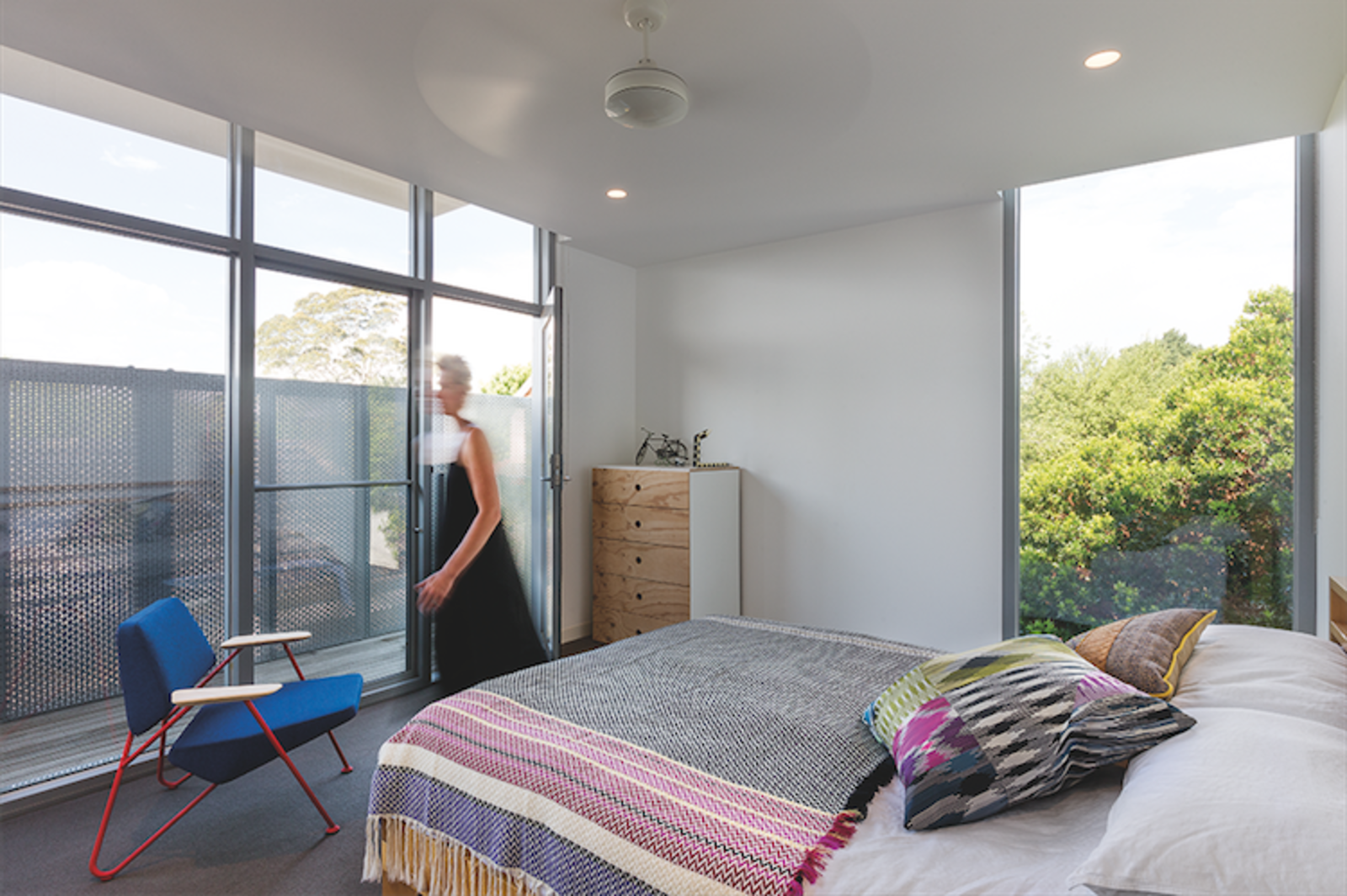 The same perforated aluminum employed for the fence is used as a privacy screen in the bedroom. The holes in the screen allow for light to spill through. Angular Australian House Fits a Family's Active Lifestyle - Photo 4 of 7