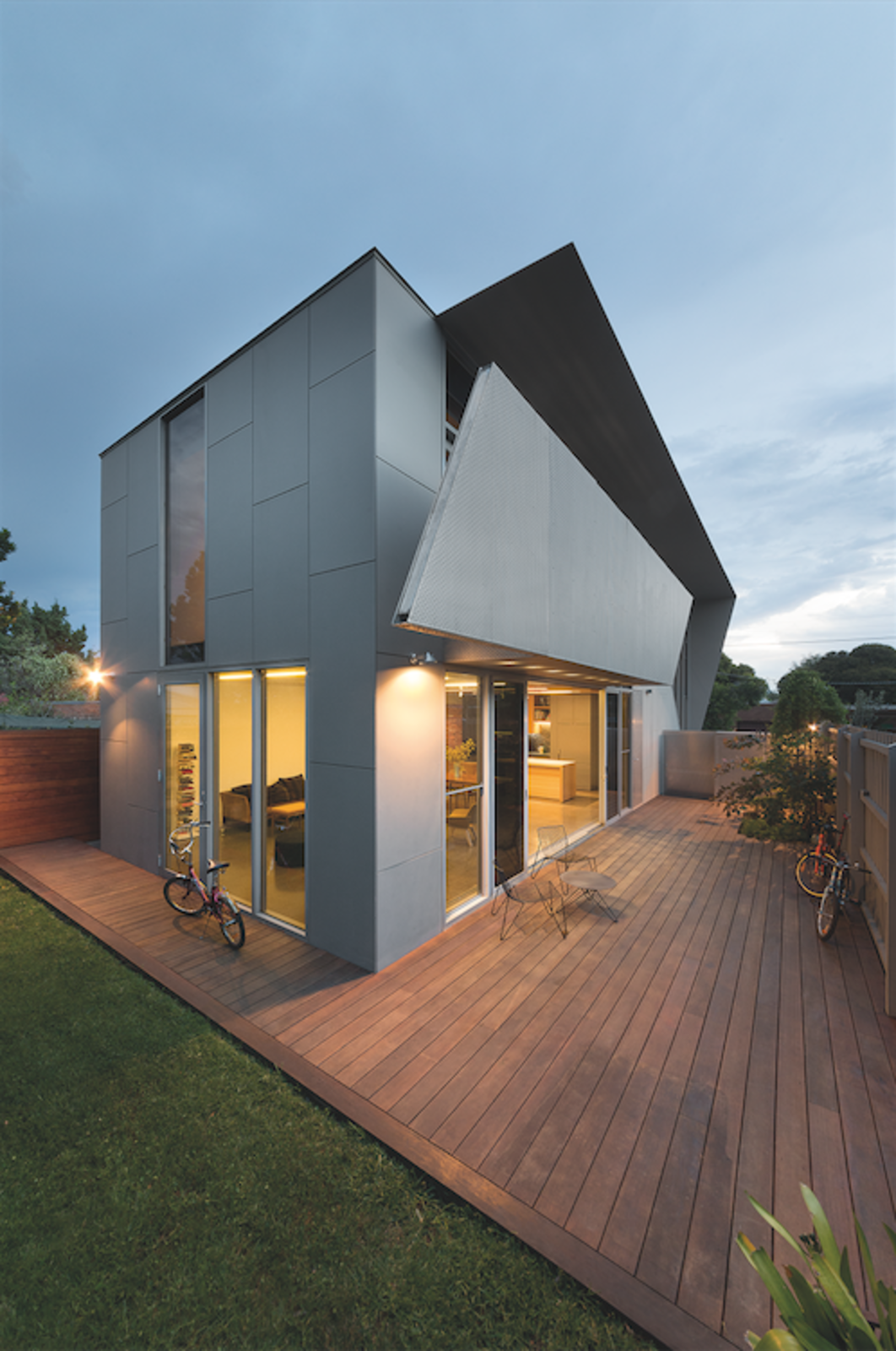 The family built the rich wood deck in the backyard, a warm visual contrast to the cold concrete and steel building. On the south side, a carefully concealed shed houses more bicycles and tools.  Photo 7 of 7 in Angular Australian House Fits a Family's Active Lifestyle