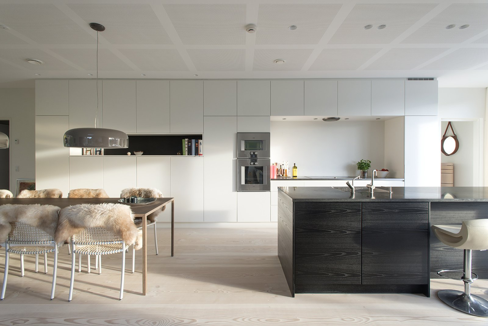 Built-in kitchen cabinets and a monolithic island help keep the space uncluttered. The wall ovens are from Gaggenau. Tagged: Kitchen, White Cabinet, and Light Hardwood Floor.  Kitchen by Claudio Torres Faini from Scandinavian Kitchens We Love