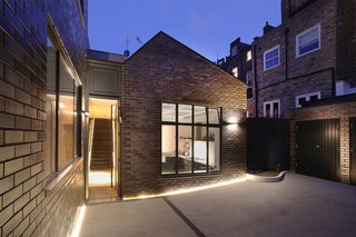 10 Dwell-Approved, New-Old Homes in the UK - Photo 1 of 18 - The renovated industrial compound is clad in metallic bronze-glazed bricks from Modular Clay Product, which match the neighboring Victorian terrace homes. The reflective bricks change in appearance as the sun moves through the sky, but always echo the Bronze Casements by Vale windows.