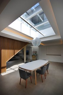 10 Dwell-Approved, New-Old Homes in the UK - Photo 2 of 18 - In the dining room, a James Burleigh table sits beneath a sizeable skylight. Throughout the ground floor, additional lighting is recessed in the coffered ceilings. Painted brick walls provide a reminder of the building's industrial past.