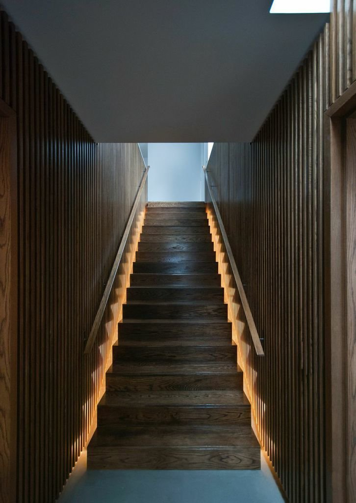 The house's central staircase is encased in oak paneling, which brings added warmth and texture to the ground floor. The wide steps rise to the second floor, which houses three bedrooms and bathrooms.