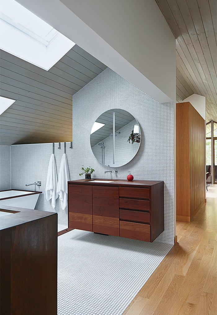 The master bathroom has an aluminum-shell tub with an ipe-slat basin, and a pair of solid-walnut vanities, all designed by Hufft Projects.  Photo 9 of 10 in This Kansas City Home Looks Like Its Neighbors, But Reveals a Truly Modern Sensibility