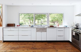 A Mind-Bending Renovation Brings a Bold, Modern Addition to an Old Farmhouse - Photo 7 of 22 - The new custom kitchen is situated in the original structure. The window is a new commercial unit with an operable frameless center pane and was set so that the countertop could tuck right underneath it to create a 1/4-inch shadow line.