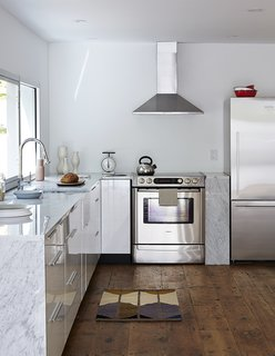 A Mind-Bending Renovation Brings a Bold, Modern Addition to an Old Farmhouse - Photo 9 of 22 - The updated kitchen is outfitted with stainless steel appliances, including a Bosch range, a Fisher & Paykel refrigerator, and a Frigidaire range hood. The faucet is Hudson Reed.