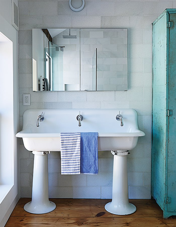 The bathroom features a salvaged 1920s schoolhouse sink from Olde Good Things. The faucet mixers are by Jado; the original single tap openings were enlarged to fit them, and the entire sink was re-glazed.  Photo 14 of 22 in A Mind-Bending Renovation Brings a Bold, Modern Addition to an Old Farmhouse