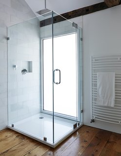 10 Best Modern Showers to Inspire Your Bathroom Renovation - Photo 6 of 10 - A glass-lined shower with a Hudson Reed shower head adds a modern touch to the second-floor bathroom in this farmhouse renovation. A pane of privacy glass lets natural light enter the room, illuminating the shower stall.