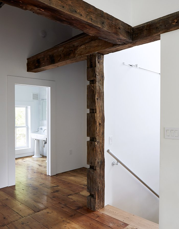 "In the existing house, the wood beams were hidden under sheetrock and wallpaper. ""I exposed them all, but I didn't let that dictate where the new walls would go,"" Givone says. ""I let the beams fall where they may.""  Farmhouse by Virginia Arrigucci from A Mind-Bending Renovation Brings a Bold, Modern Addition to an Old Farmhouse"
