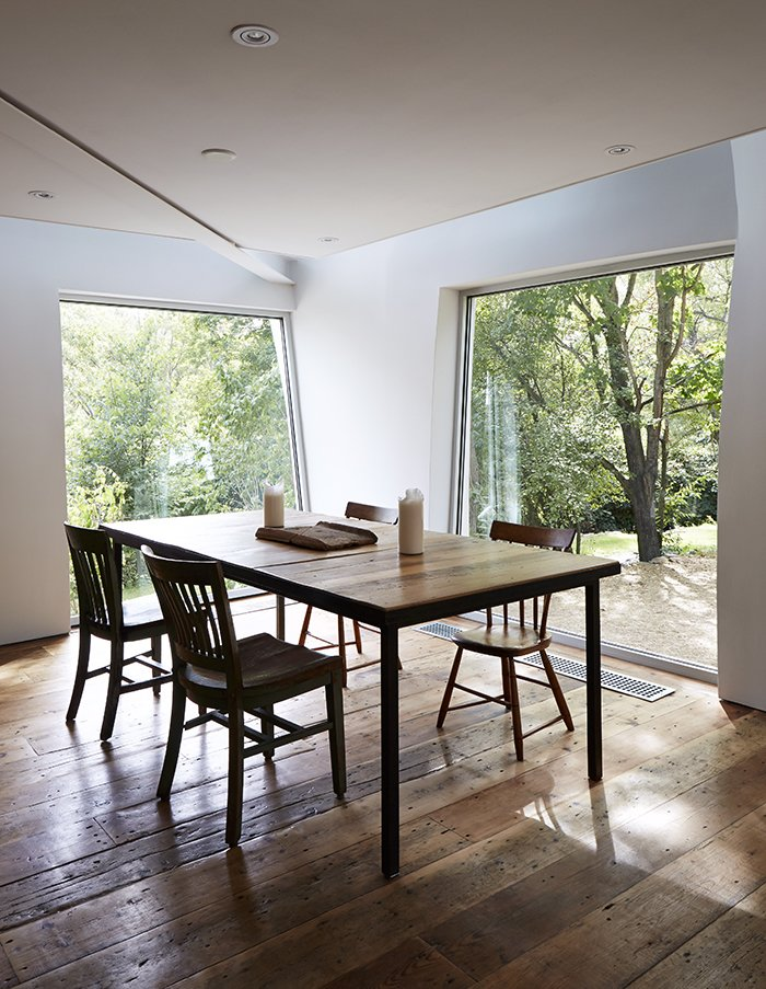 The new dining area is surrounded by swathes of glass. The windows were pivoted and installed at unusual angles in order to accommodate the undulating walls of the addition. A Mind-Bending Renovation Brings a Bold, Modern Addition to an Old Farmhouse - Photo 17 of 22
