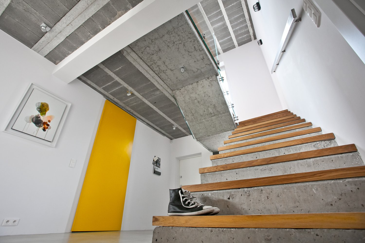 "Ceilings are typically composed of concrete beams and blocks that are covered with drywall and paint. But for this project, the architects left them bare to texturize the room. ""It creates a beautiful contrast with the snow white walls and splashes of yellow,"" they explain. The painting on the wall is by Magdalena Karpińska. 190+ Best Modern Staircase Ideas by Dwell"