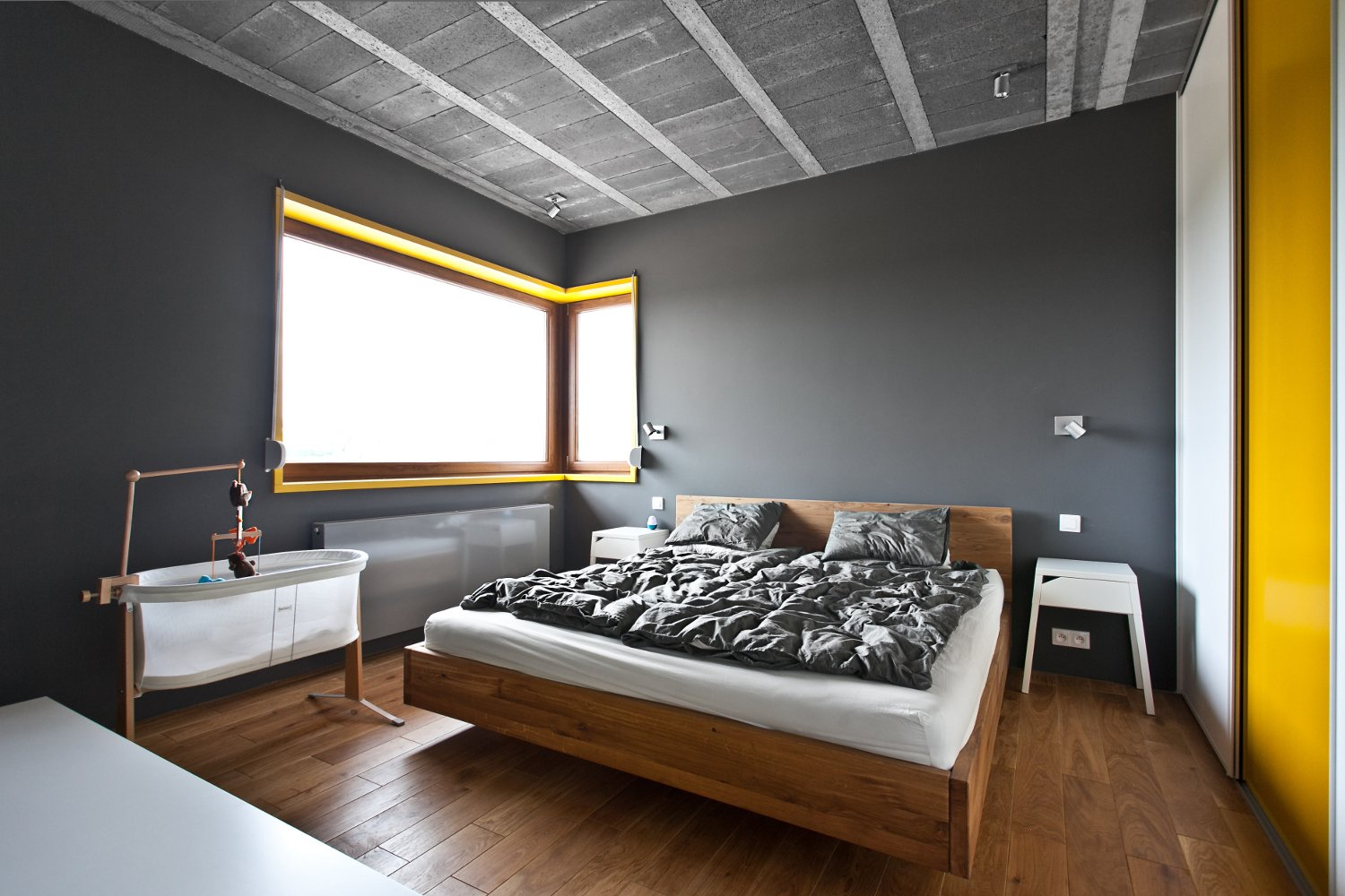 The bedrooms feel like sanctuaries, as they're much darker and enclosed than other spaces in the home.  Bedroom by Dane Cupp from A Modern Home Experiments with Exposed Concrete and Sliding Yellow Doors
