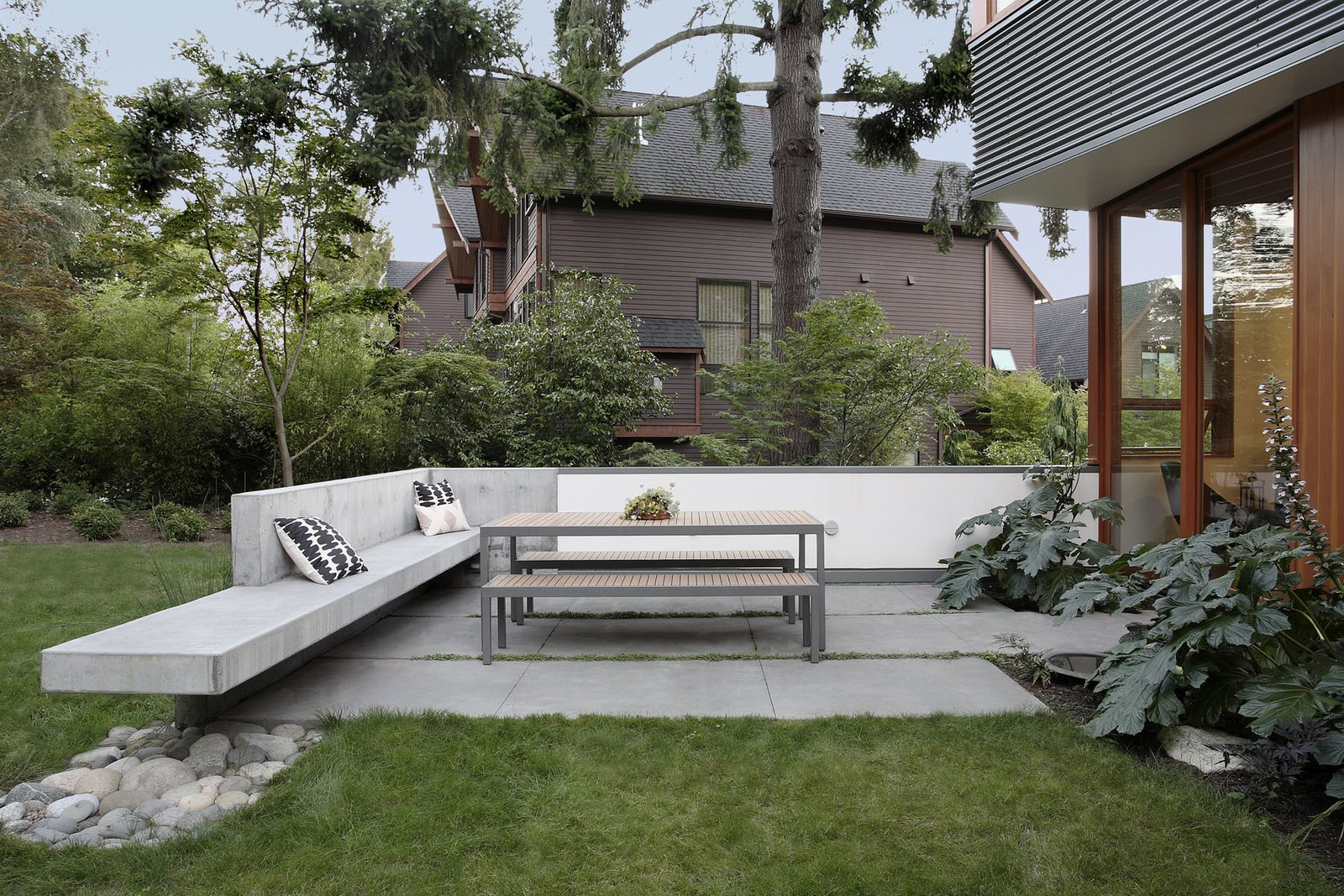 "A patio spins off the northern end of the house's main level. It fronts ""Main Street,"" which unwinds from the heart of downtown Seattle into a pedestrian foot path bordered by a woodland. ""We went with a low and robust barrier instead of a tall wood fence to preserve views to the park,"" Schaer says. The table and benches are by Crate & Barrel."