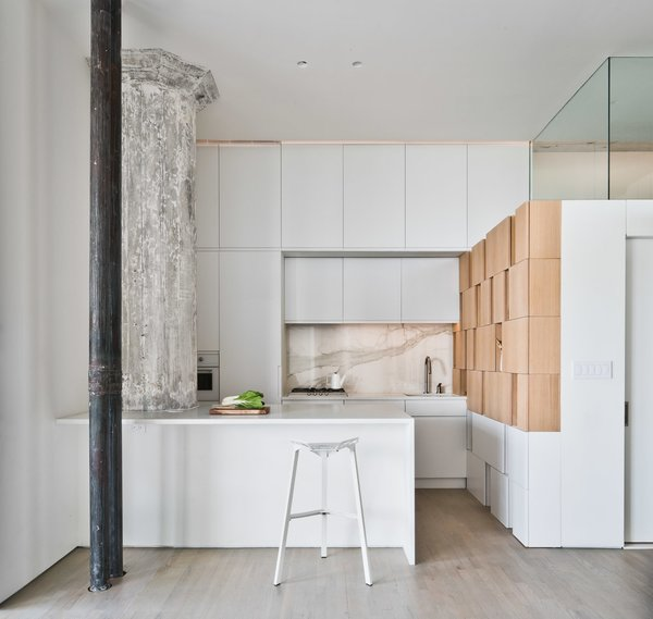 The careful coordination of color continues in the kitchen, where the gray and white marble backsplash, lit with faint orange lights, mediates between the ashen column and ochre cabinets. Tagged: Recessed Lighting.  Photo 16 of 21 in Mad About Marble: 20 Kitchens and Bathrooms
