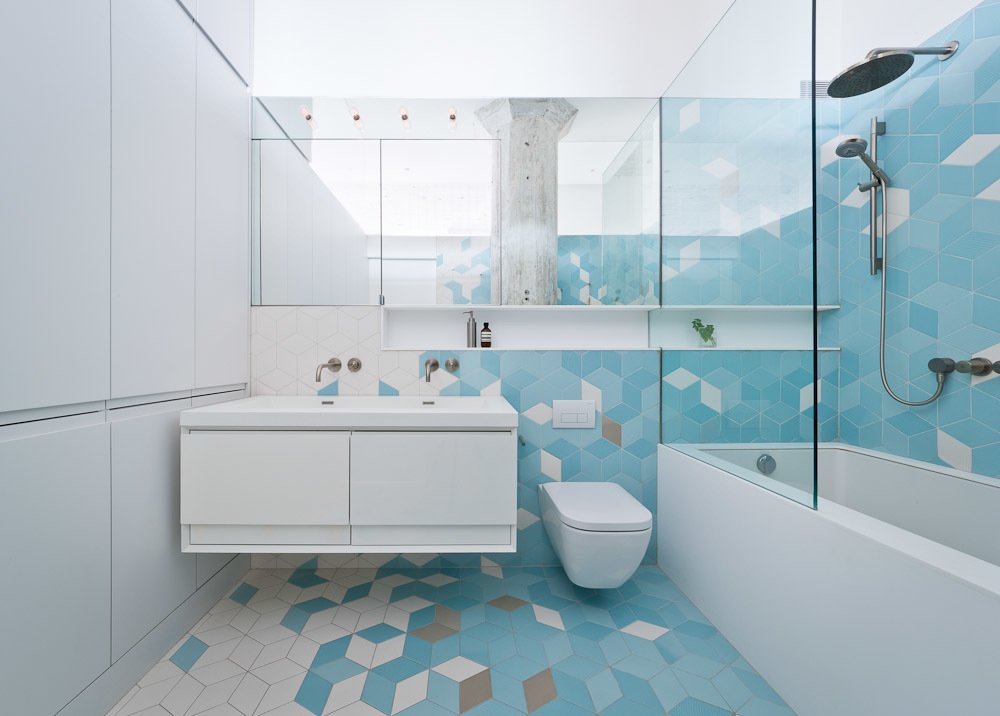 The bathroom, located just adjacent to the kitchen, features a pattern of gray and turquoise tiles that climbs from the floors up the walls. They serve as a burst of color among the predominately white walls elsewhere, transforming the bathroom into one of the apartment's most striking spaces. Tagged: Bath Room, Wall Mount Sink, Alcove Tub, Ceramic Tile Floor, Ceramic Tile Wall, One Piece Toilet, and Open Shower.  Photo 3 of 20 in 20 Bathrooms With Transformative Tiles from Brooklyn Loft Renovation Masters Storage with a Custom Cabinet Wall