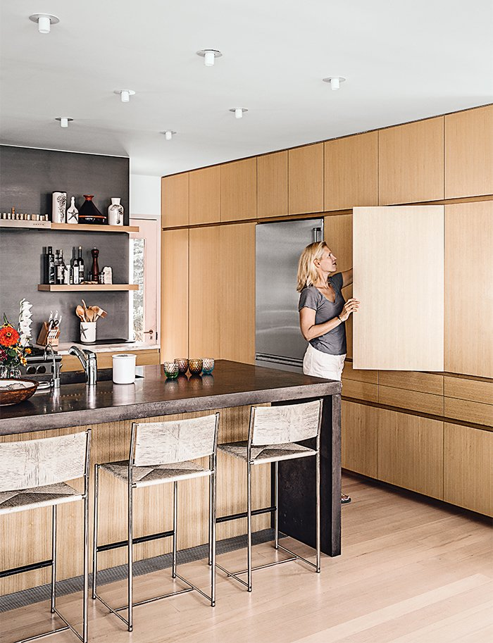 Kitchen cabinets in Japanese elm are topped with Calacatta marble and wraparound concrete for the island.