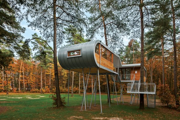 Photo Essay: Enchanting Tree Houses - Photo 4 of 24 - To reduce impact at the site, Baumraum prefabricated the house and craned it atop 19 steel columns, arranging it so that the surrounding trees' roots wouldn't be harmed. From within the structure, people experience a perspective that inspires more respect and consideration of the environment at large.