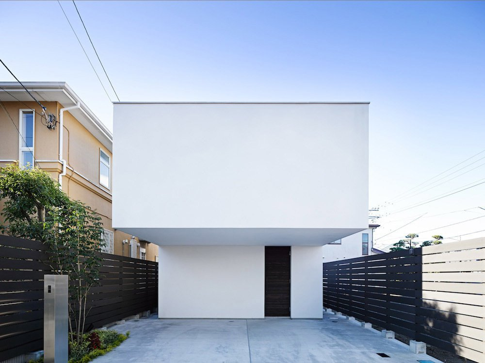 The façade designed by Apollo Architects and Associates features an overhanging upper level, which ensures that the entrance is pleasantly shaded and demarcates the property's two parking spaces. The home's wooden structure is clad in a bright white exposed concrete.  Unabashedly Strange Houses in Japan by Luke Hopping from This Modest Japanese Home is a Surfer's Paradise