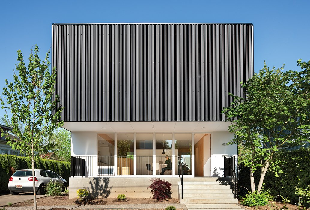 Architect Ben Waechter wrapped the upper floor of Nick Oakley's house in inexpensive black corrugated steel. By rounding the corners, Waechter avoided unsightly trim at the edges.  Photo 1 of 9 in An Industrial Designer's House Blends Economy and Simplicity