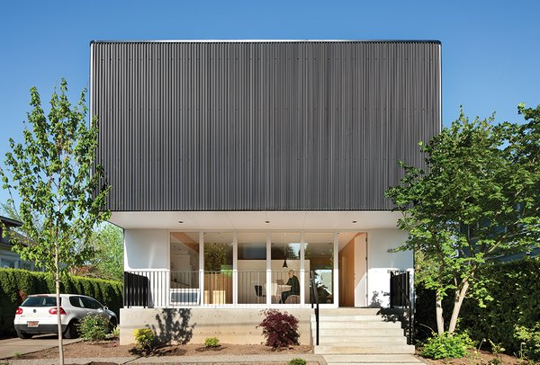 Architect Ben Waechter wrapped the upper floor of Nick Oakley's house in inexpensive black corrugated steel. By rounding the corners, Waechter avoided unsightly trim at the edges.