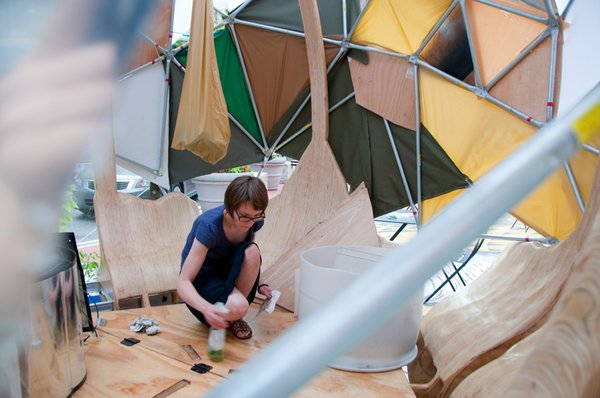 A volunteer prepping the interior of one of the geodesic-inspired Flock Houses.