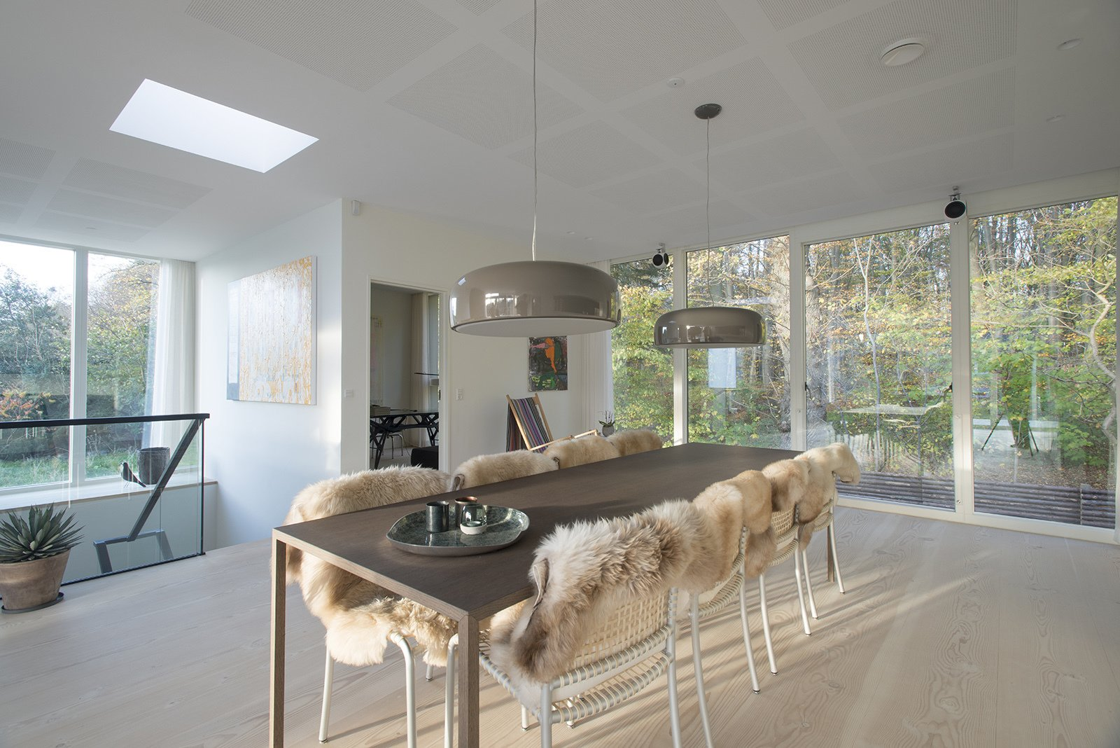 Smithfield pendant lights by Jasper Morrison for Flos illuminate the dining table. Natural wood floors and neutral hues create a spare, yet warm, aesthetic.  Villa R by Diana Budds from Modern Homes in the Forest