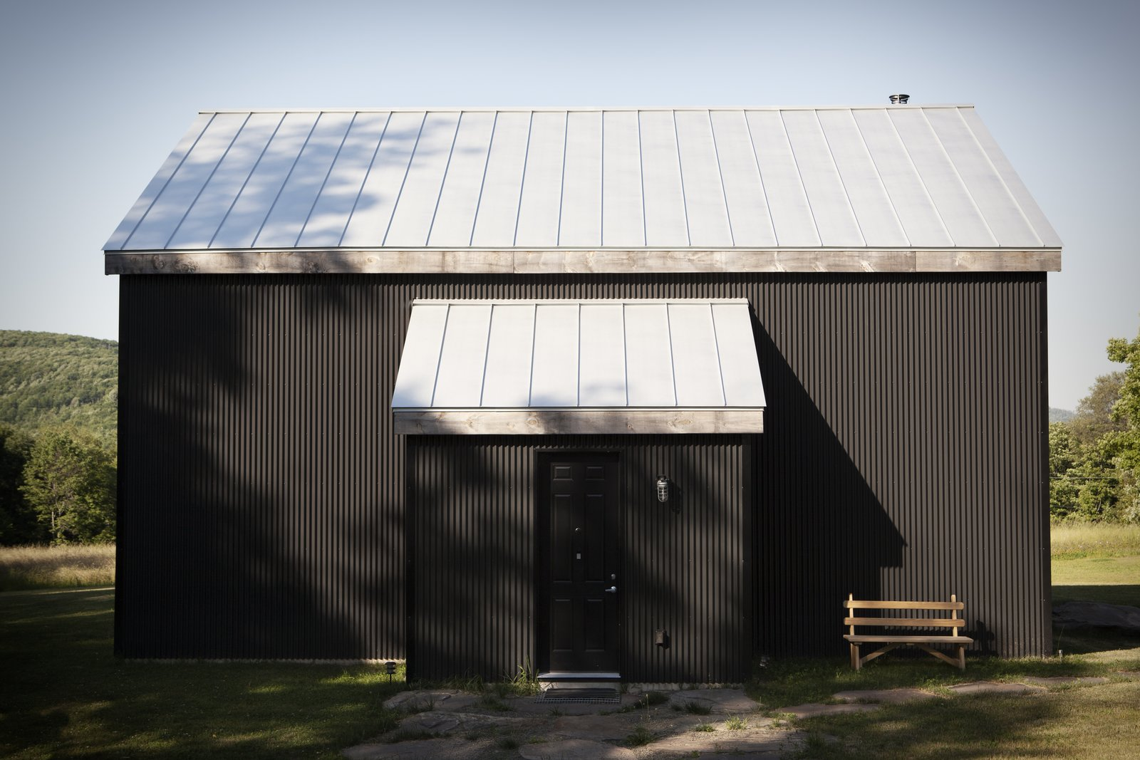 "In Scandinavian regions, traditional cabins are painted black using a mixture of tar and linseed oil. Peck reproduced the look using corrugated metal—a lower-maintenance, more sustainable material. ""We love that it is black, because it really reminds us of home,"" Bronee says. The house has no windows on its front side, belying its light-flooded interior. Tagged: Exterior, Cabin Building Type, and Metal Roof Material.  30+ All-Black Exterior Modern Homes by Zachary Edelson from A Slice of Scandinavian Design in the Catskills"
