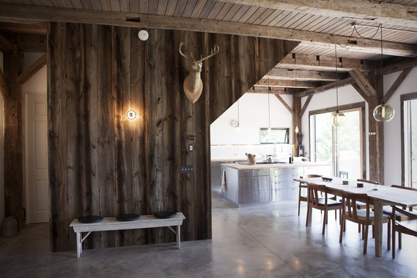 "The cabin's basic structure was reclaimed from a barn built in 1840 and purchased from Heritage Barns out of Waco, Texas. The same company supplied the recycled wood that clads the walls, though the ceiling boards are new. ""We stained them with a gray wash to match the tones of the post and beam, but with a more clean look,"" Bronee explains. The concrete floors were polished and waxed for a sleek finish."