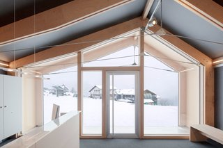 "This Prefab Ski School in the Alps Took 10 Days to Assemble - Photo 3 of 7 - Girodo says the ""high insulation performance of the shell"" allows the building to function in a setting that experiences significant temperature fluctuations and extreme cold. Occupants of the front room, which functions as a reception area, can take in the views from its full-height windows in complete comfort."