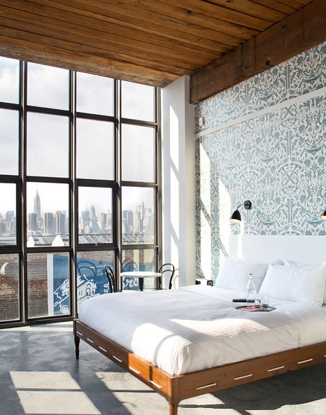 A bedroom with a view of Manhattan in the Wythe Hotel.  Bedroom by Maya Dunne + Associates  from Photographers We Love: Mark Mahaney
