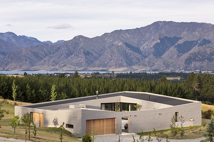 Breaking up the roof planes and concrete floor plates allowed the house to blend into the landscape. The wall that wraps the building ensures it is still a single, coherent form.  Lake Hawea Courtyard House by Sam Eichblatt
