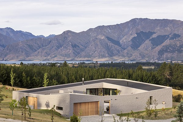 Breaking up the roof planes and concrete floor plates allowed the house to blend into the landscape. The wall that wraps the building ensures it is still a single, coherent form. Photo 3 of Lake Hawea Courtyard House modern home