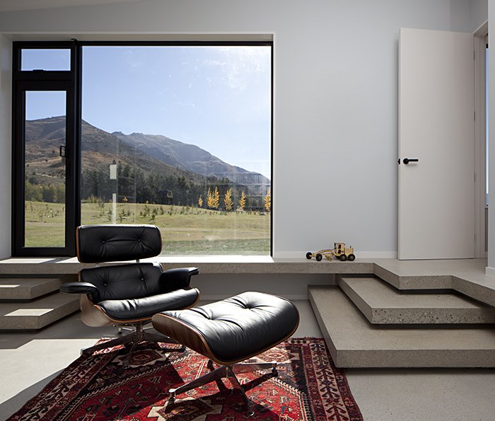 The clients intend to retire to the house. They asked that rooms be constructed flexibly on a non-domestic scale. This one, with an Eames lounge and floor-to-ceiling glass windows, frames a serene mountain vista like a painting.  Lake Hawea Courtyard House by Sam Eichblatt