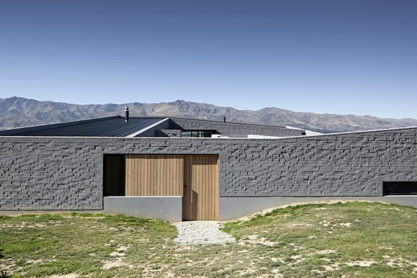 The protective wall is broken with small apertures, like this wood-panelled door that slides back to allow entry. Photo 6 of Lake Hawea Courtyard House modern home