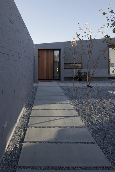 With its expansive, geometric design and wide concrete-slab walkways, the enclosed central courtyard around which the house is organized creates outdoor space protected from the sometimes-inhospitable wind out of the northeast. Photo 8 of Lake Hawea Courtyard House modern home