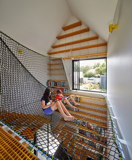 This Transformed Melbourne House Resembles a Quirky Village - Photo 3 of 11 - Spinning off the living room on the north side of the main house, the children's study sits separately from the other pavilions. On its upper level, Oxley netting forms a web on which the kids and their friends can sit and read with views of the leafy street and garden.