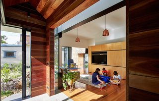 "This Transformed Melbourne House Resembles a Quirky Village - Photo 5 of 11 - The owners furnished the living room with a mixture of new and old pieces, including a Hans Wegner lounger and Tuckbox coffee table. A timber-lined hallway leads out from it to the newer parts of the home. Sections of steel-framed double glazing separate and accentuate each ""house"" while letting in glimpses of sky."