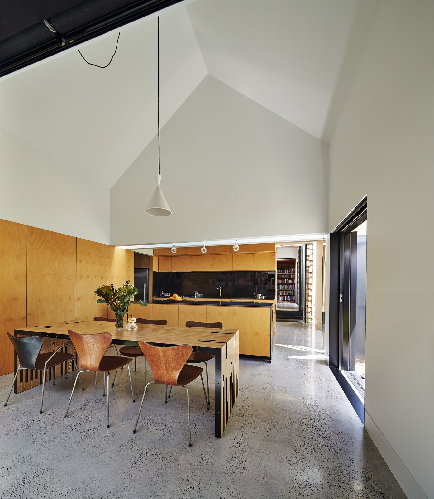 """The dining room serves as the hub for all activity. Original Series 7 chairs by Arne Jacobsen complement a table Maynard designed and dubbed the """"Zero Waste Table,"""" since it utilizes every inch of a large wood sheet. To the right, a sliding door opens to the garden. Tagged: Dining Room, Pendant Lighting, Chair, and Table.  Photo 7 of 12 in This Transformed Melbourne House Resembles a Quirky Village"""