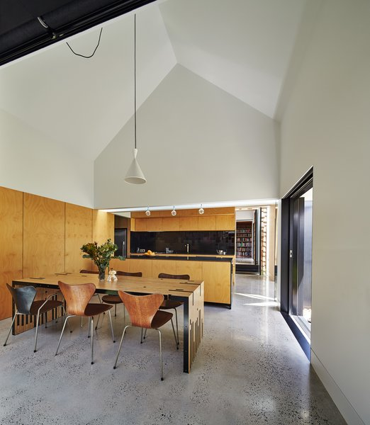 "The dining room serves as the hub for all activity. Original Series 7 chairs by Arne Jacobsen complement a table Maynard designed and dubbed the ""Zero Waste Table,"" since it utilizes every inch of a large wood sheet. To the right, a sliding door opens to the garden."