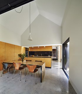 "This Transformed Melbourne House Resembles a Quirky Village - Photo 6 of 11 - The dining room serves as the hub for all activity. Original Series 7 chairs by Arne Jacobsen complement a table Maynard designed and dubbed the ""Zero Waste Table,"" since it utilizes every inch of a large wood sheet. To the right, a sliding door opens to the garden."